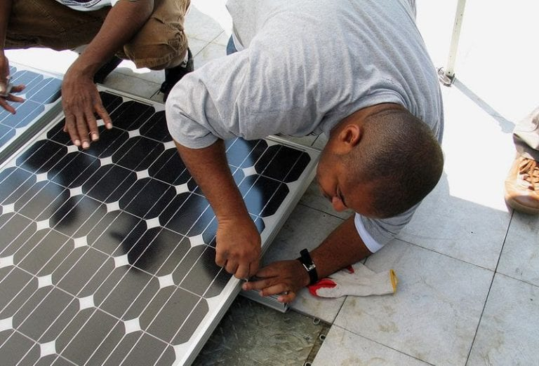 Photo of a man working on a solar panel